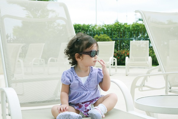 adorable young baby girl wearing sunglasses in flirting position